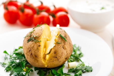 Hot baked potato with butter on a white plate Stock Photo