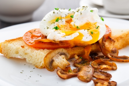 Poached egg with mushrooms and tomatoes on a plate