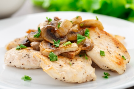 Gebakken kipfilet met champignons en peterselie Stockfoto
