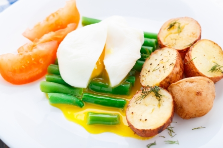 baked beans: Poached egg with french beans and baked potato on a plate