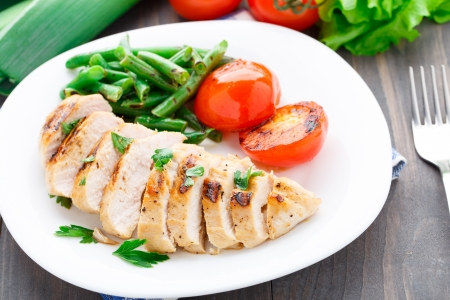 Gegrilde kip met groene bonen en tomaten op een plaat Stockfoto