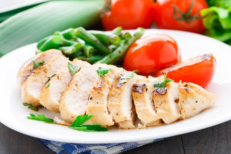 Grilled chicken with green beans and tomatoes on a plate