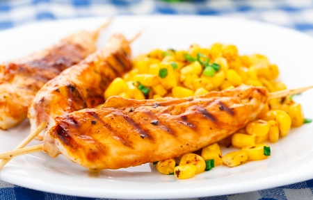 Honey chicken skewers with grilled corn salad on a plate photo