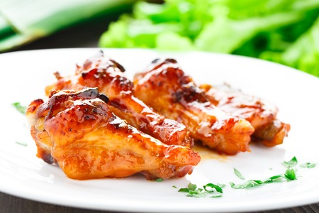 Delicious chicken wings with honey sauce on a plate