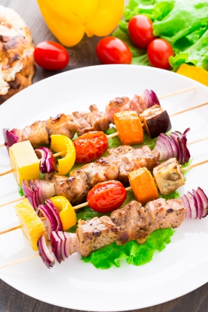 Barbecued pork and vegetable kebabs on a plate photo