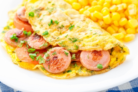 Omelet with sausage, tomato and herbs on a plate