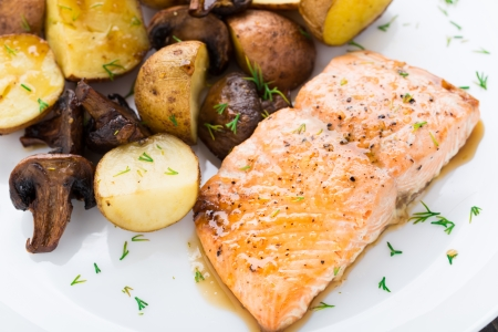 Roasted salmon with potatoes and mushrooms on a plate photo