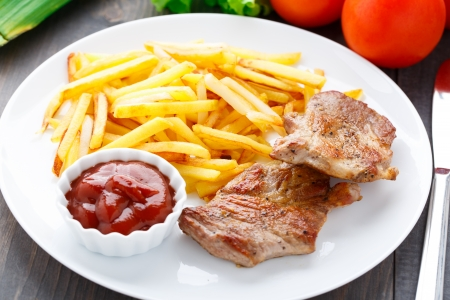 Fried steak with french fries and ketchup on a plate photo