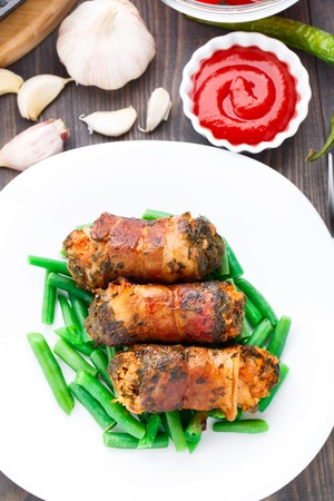 Delicious bacon wrapped cutlet with green beans photo
