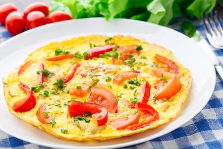 Omelet met paprika, tomaat en kruiden op een bord Stockfoto