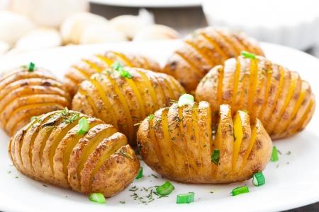 jacket potato: Accordion baked potatoes on a white plate
