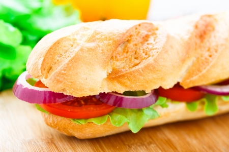Vegetarian baguette sandwich with lettuce, tomatoes, pepper and onion
