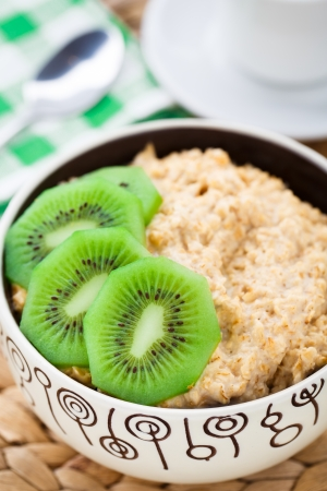 Bowl of oats porridge with kiwi on a table photo