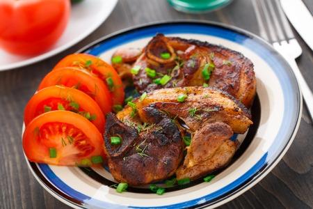 pan fried: Pan fritto braciola di maiale con l'osso servito con pomodori