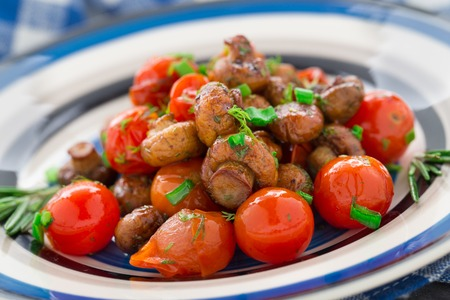 buttom: Roasted mushrooms with cherry tomatoes on a plate Stock Photo