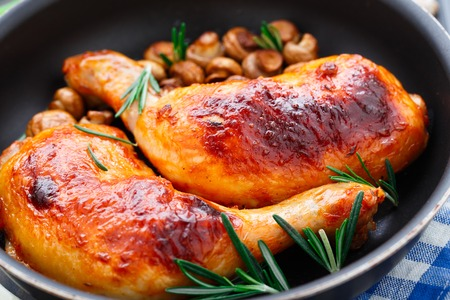 chicken meat: Roasted chicken legs with mushrums in a pan