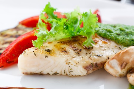 Grilled fish fillet with vegetables on a plate photo