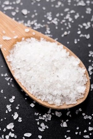 Sea salt in wooden spoon on a black table photo