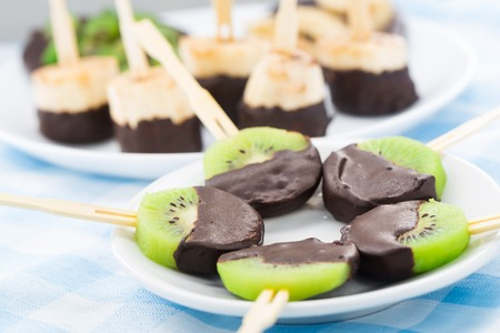 Fresh fruits with chocolate on a stick