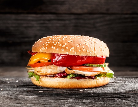 Burger with chicken and vegetables on a rustic background