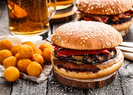 beef burger: Delicious burgers with fried potato balls and beer on a rustic table Stock Photo