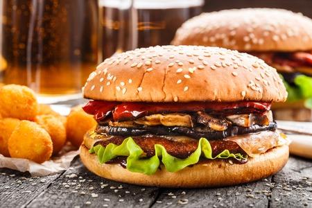 hamburguesa: Hamburguesas deliciosas con bolas de patata fritas y cerveza en una mesa r�stica Foto de archivo