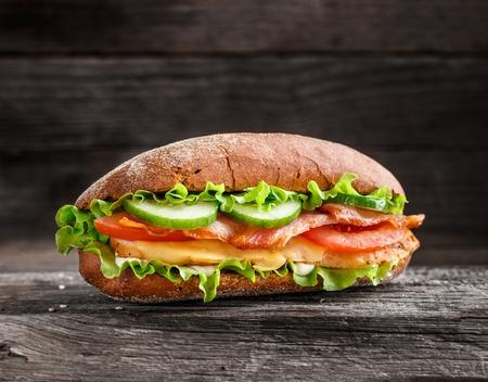 Sandwich met kip, spek kaas en groenten op een rustieke achtergrond