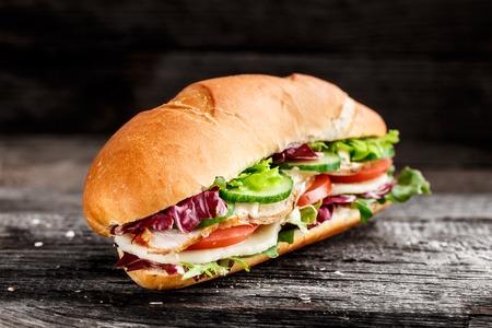 bocadillo: Sandwich de pollo, queso y verduras sobre un fondo rústico