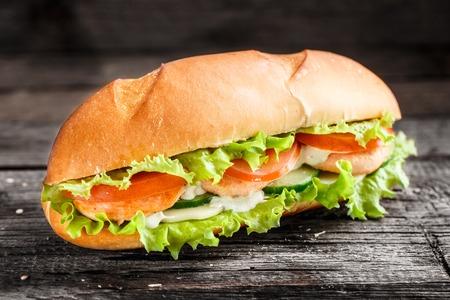 bocadillo: Emparedado con la hamburguesa de salm�n y verduras sobre un fondo r�stico