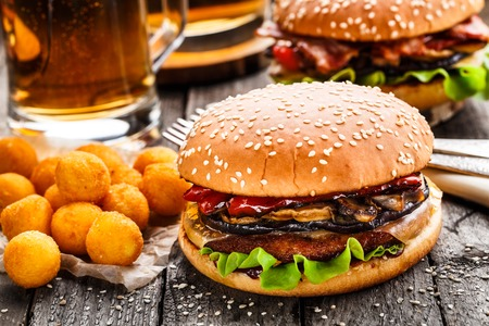Delicious burgers with fried potato balls and beer on a rustic table Stock Photo