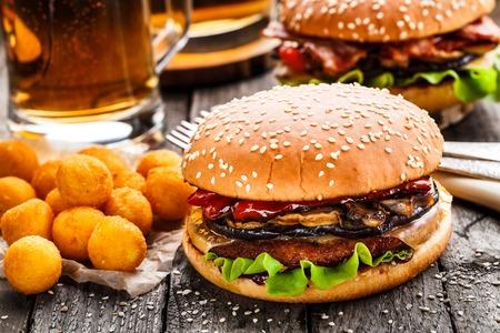 Heerlijke hamburgers met gebakken aardappel ballen en bier op een rustieke tafel Stockfoto