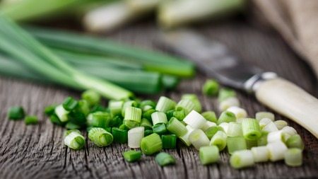 scallions: Chopped scallions on a rustic wooden board