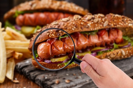 food inspection: Someone examining hot dog with magnifying glass in a hand Stock Photo