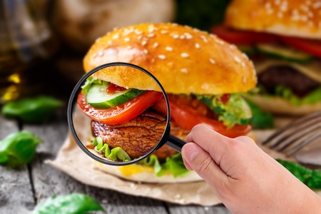 vegetarian hamburger: Someone examining burger with magnifying glass in a hand Stock Photo
