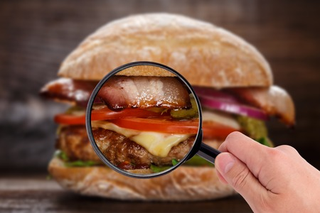 Someone examining burger with magnifying glass in a hand Stock Photo