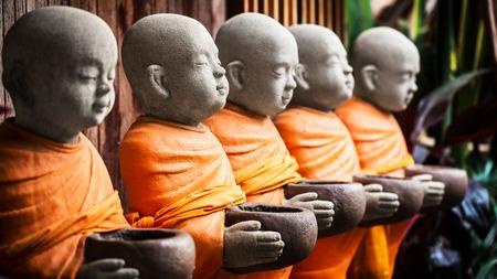 monk robe: Monk statue in orange robe holding bowl in hands Stock Photo