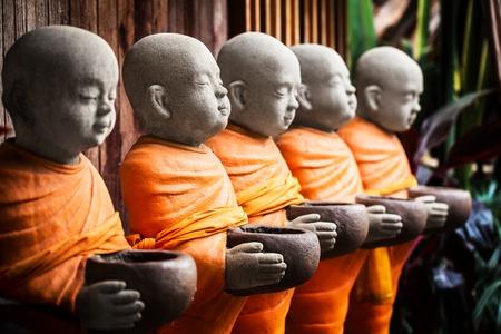 Robe: Monk statue in orange robe holding bowl in hands Stock Photo