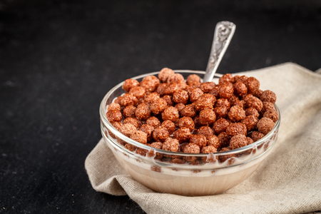 chocolate cereal: Healthy breakfast. Chocolate cereal balls in bowl with milk on slate background.