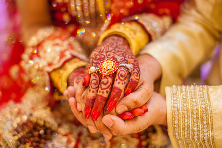 Indian wedding hands with gold Standard-Bild