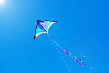 Triangle kite flying on a sunny day blue sky