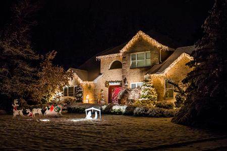 Ingericht huis voor Kerstmis 's nachts bedekt met sneeuw