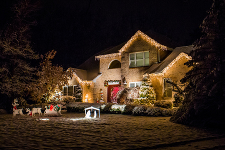 Decorated house for Christmas at night covered in snow