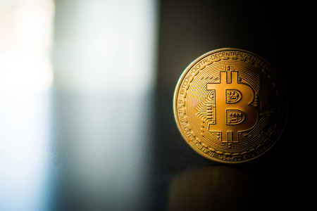 Single bitcoin coin close up on the surface standing Reklamní fotografie