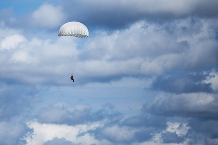 Parachutist descending from above with a white round canopy Stock Photo