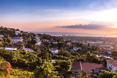 De heuvels van de Kingstonstad in de zonsondergang van Jamaïca