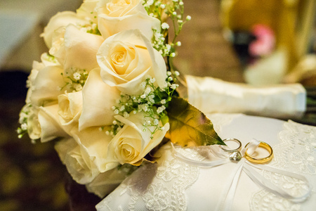 Wedding bouquet of roses with two rings on a pillow