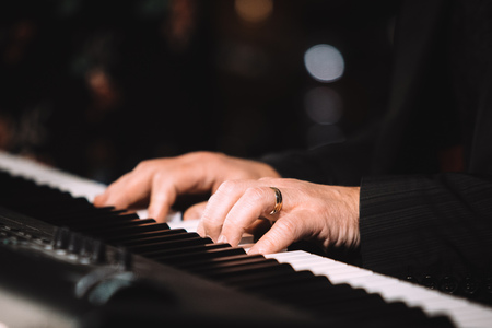 Close up male hands playing electric piano indoors