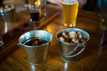 Bar buckets with raw peanuts and beer on the background