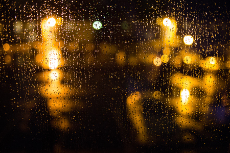 Rain drops on window. Peaceful evening or night at home when raining outside. Water drops on glass. Surface of wet glass. Water splash. City lights bokeh during the rain.