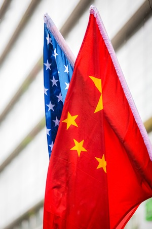 Chinese and American flags together outside at day Stock Photo